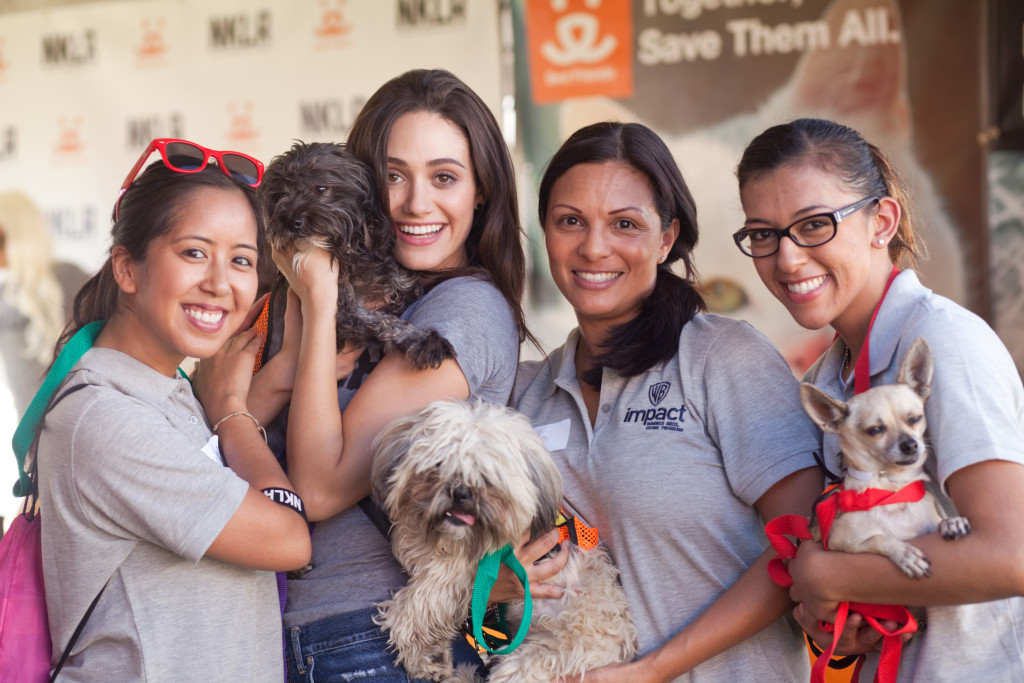 Emmy Rossum and volunteers from Warner Bros snuggle with adoptable pups at the Best Friends NKLA Adoption Weekend